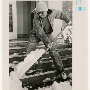 Man shovels snow from Turlington Hall steps