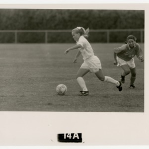 Womens soccer player drives the ball
