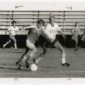 NCSU soccer player runs ball by Duke defender in womens soccer finals