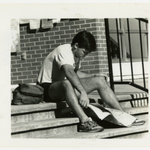A student reads the newspaper on a warm October day in front of the Student Center