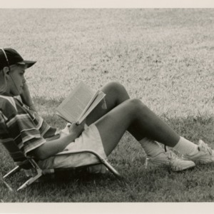 Freshman, reading a book, relaxes at Tucker Beach