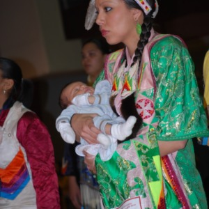 Woman in traditional dress holding baby at NC State's Native American Student Association Pow Wow