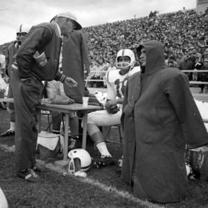 Coach Earle Edwards discusses strategy with his 1961 team captain, Roman Gabriel (seated)