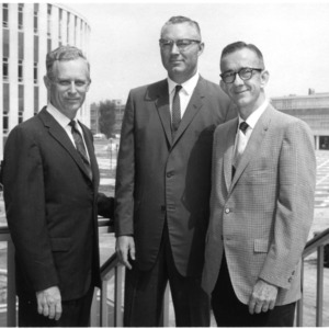 William M. Roberts, J. Edward Legates, and Marvin L. Speck in front of Harrelson Hall and Student Union Building