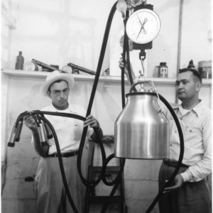 Men displaying milking machine