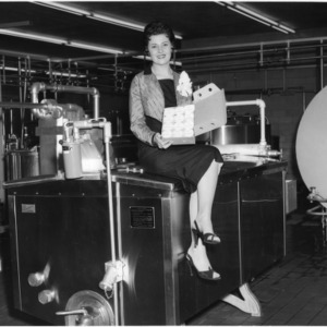 Patricia Simonds, Dairy Princess 1957, displaying box of N.C. State College ice cream during Dairy Month