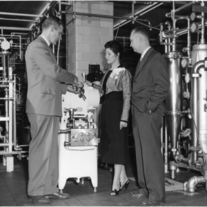 Patricia Simonds, Dairy Princess 1957, being shown dairy processing equipment at North Carolina State College