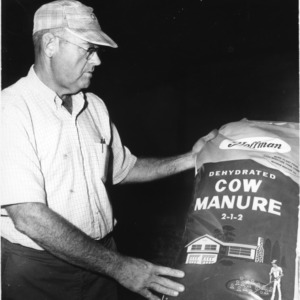 Ranch Manager Ed Hollowell with bag of fertilizer