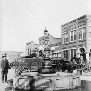 A horse drawn carriage stops at a fountain