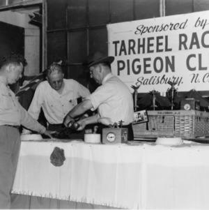 J.W. Carpenter, Salisbury, Demonstrates Banding of Racing Homers, 1952 State Fair