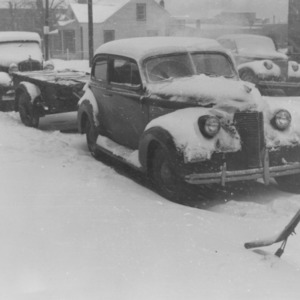 Cars covered with snow during storm