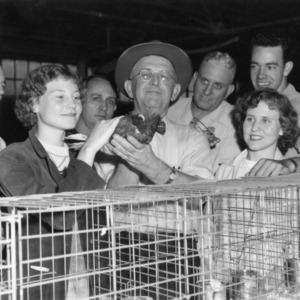J.W. Carpenter shows prize pigeons to admirers, 1952 N.C. State Fair
