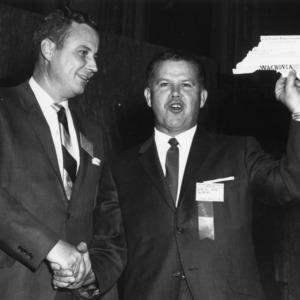 Dr. W. C. Mills, Jr. presenting Gene R. Waite with check at North Carolina Turkey Federation Conference