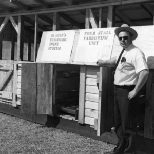 Man standing in front of display of Bladen's Economic Swine System, Four Stall Farrowing Unit
