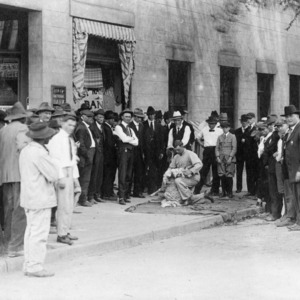 Crowd watching sheep shearing demonstration in front of First National Bank