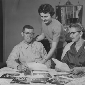 W. C. Templeton family looking at photographs of 4-H activities and accomplishments