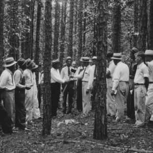 County Agent D.H. Sutton presenting an axe as prize in thinning contest