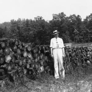 John Brown in front of shortleaf pine billets