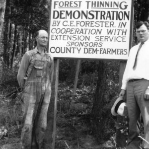C. E. Forester and Mr. Haney in front of sign notifying forest thinning demonstration