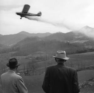 Men watching plane dusting field with fertilizer