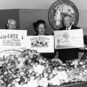 """Governor Dan Moore, extension specialist Mel Kolbe, and extension agent Mary Cornwell promoting """"Apple Week"""""""