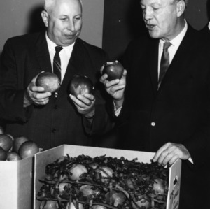 "Governor Dan K. Moore and horticulture specialist Mel Kolbe promoting ""Apple Week"""