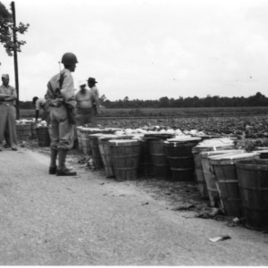 Military men with baskets of vegetables