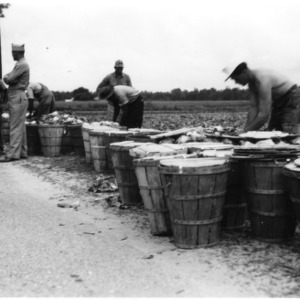 Military men and others with baskets of vegetables
