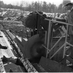 Man overseeing saws used on logs