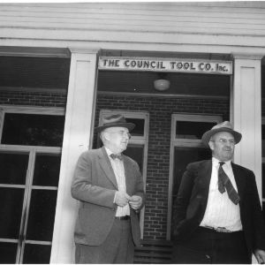 Clyde Council and John Council in front of The Council Tool Co. Inc. building