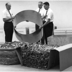 Three men examining bundles of cured tobacco
