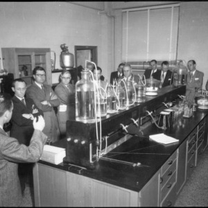 Man speaking to group in a laboratory, Farm Press and Radio Institute