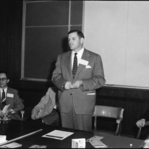 Man addressing group in conference room, Farm Press and Radio Institute