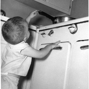 Home safety demonstration photograph showing a child reaching for a pot handle