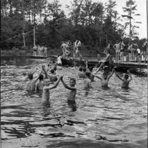 Water safety demonstration photograph showing boys swimming in pairs