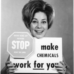 Billie Gale Norman displaying a sign to promote pesticide and chemical safety