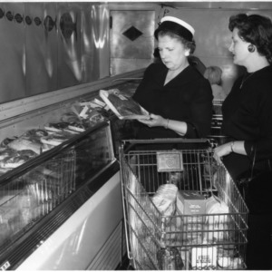 Miss Dora Ferrell showing Mrs. Wilton Fish the characteristics of high quality meat at the supermarket