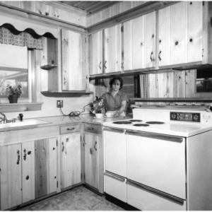 """Mrs. James Grady """"pouring"""" in her new kitchen"""