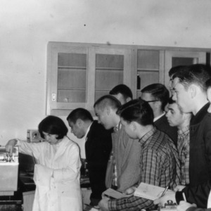 Students observing woman conducting agricultural research