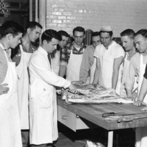 Group of men observing butchering