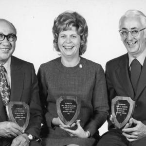 J. A. Spaulding, Mrs. Elizabeth Meldan, and Dr. W. G. Andrews pose with Coastal Plains Development Association awards