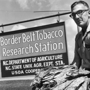 Man with tobacco with sign for Border Belt Tobacco Research Station