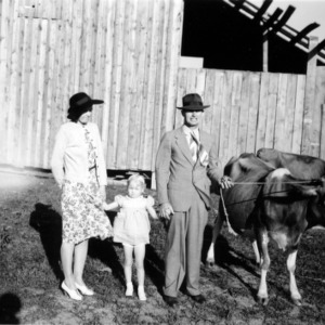 Dairy farmer J. C. Turner with wife, daughter, and two cows