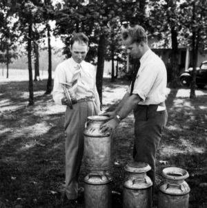 Dairy farmer J. C. Turner and farm agent J. E. Zimmerman examining milk cans