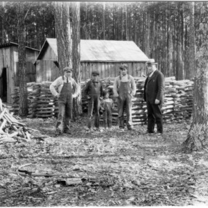 Men and boy in front of stacks of fuelwood