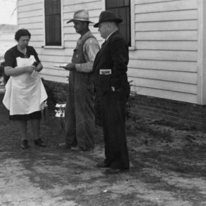 Mr. and Mrs. J. E. Murphy delivering their first can for new milk route and receiving instruction from Agent Neil M. Smith