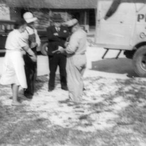 Mr. and Mrs. B. D. Adcock receiving instructions from Agent Neil Smith and dairy representative Farrier on keeping milk