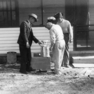 J. T. Adcock, J. W. Adcock, and another man with concrete milk cooler