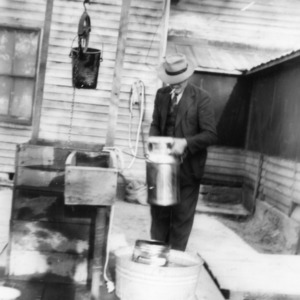 J. T. Adcock placing milk can in well to cool