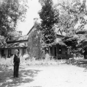 Agent T.J.W. Broom in front of former house
